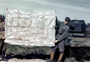 Finnish Soldiers displaying a map of the Soviet Union captured at the Porlampi motti, autumn of 1941. In the background is a T-37A amphibious tank.