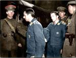 Two Luftwaffe prisoners of war (an Unter and an Oberfeldwebel) being put aboard a train under escort by soldiers and an MP.