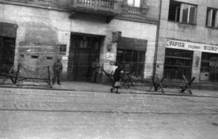 "Bunker and gate of Abschnittwache Nord (so called Nordwache) building at Żelazna 75a street behind barbed wire obstacles ""Cheval de fries"" July 1944."