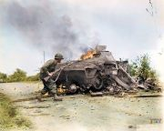An American G.I. (possibly of the 79th US Infantry Division) runs past a German Sd.Kfz 251 Ausf D (SonderKratfahrzeug 251).