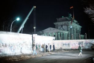 A crane removes a section of the Wall near Brandenburg Gate on 21 December 1989.