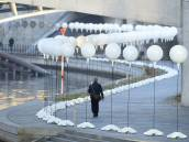 A man walks past a row of lanterns that are part of the light installation Lichtgrenze (Light border) on the course of the former Berlin wall near the Reichstag building.