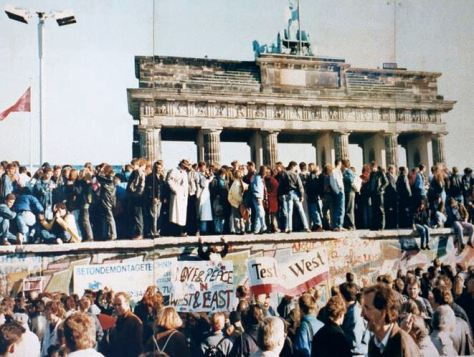 Germans stand on top of the wall in the days before it was torn down.