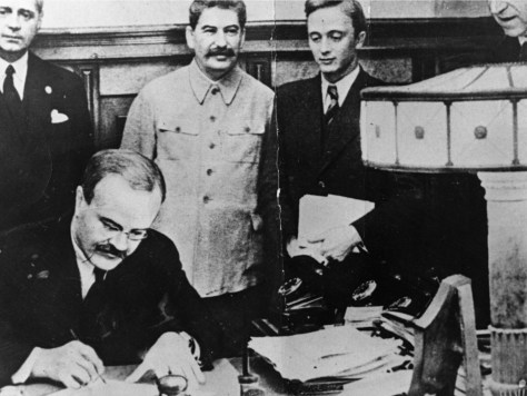 Molotov signing the Treaty of Non-aggression between Germany and the Union of Soviet Socialist Republics with Stalin and Ribbentrop in the background.