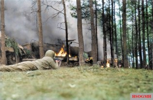 'Blazing German Convoy' A Soldier of the 311th Infantry Regiment, 78th Infantry Division, 1st US Army, uses a burning German convoy for shelter as he draws a bead on enemy in the woods near Honnef, Germany. March 1945.