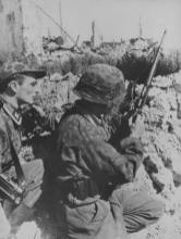 A sniper of the WaffenSS adjusted his rifle scope.