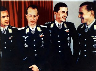 "Four top fighter aces from Luftwaffe posing together after the small awards ceremony with Adolf Hitler at Führerhauptquartier Wolfsschanze (Wolf's lair) in Rastenburg/East Prussia, 22 September 1943. From left to right: Hauptmann Heinrich Prinz zu Sayn-Wittgenstein (receiving Eichenlaub #290 zum Ritterkreuz des Eisernen Kreuzes as Gruppenkommandeur I.Gruppe / Nachtjagdgeschwader 100, after 54 night victories. Award date: 31 August 1943), Major Hartmann Grasser (receiving Eichenlaub #288 zum Ritterkreuz des Eisernen Kreuzes as Gruppenkommandeur II.Gruppe / Jagdgeschwader 51 ""Mölders"", after 103 day victories. Award date: 31 August 1943), Hauptmann Walter Nowotny (receiving both the Eichenlaub #293 and Schwerter #37 zum Ritterkreuz des Eisernen Kreuzes as Gruppenkommandeur I.Gruppe / Jagdgeschwader 54 ""Grünherz"", after 189 and 218 day victories. Award date: 4 September 1943 and 22 September 1943, all respectively), and Hauptmann Günther Rall (receiving Schwerter #34 zum Ritterkreuz des Eisernen Kreuzes mit Eichenlaub as Gruppenkommandeur III.Gruppe / Jagdgeschwader 52, after 200 day victories. Award date: 12 September 1943). The picture was taken by Walter Frentz."