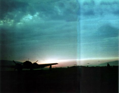 May 1941, sunrise at 7.(Fern)Staffel / Lehrgeschwader 2's base in Greece. Operations have already begun in spite of the twilight; note the three Junkers Ju 52s taking off in the background.