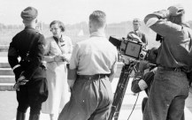 Riefenstahl stands near Heinrich Himmler while instructing her camera crew at Nuremberg, 1934.