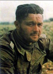"""The strain of battle is evident in the face of SS-Sturmbannführer Johann """"Hans"""" Waldmüller (13 September 1912 – 8 September 1944), commander of I.Bataillon / SS-Panzergrenadier-Regiment 25 / 12. SS-Panzer-Division """"Hitlerjugend"""" while fighting in Normandy, June 1944. He is wearing the Italian M29 Telo Mimetico camo smock."""