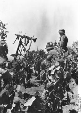 Tripod mounted MG 42 setup for its anti-aircraft role provides air cover during a rest pause.