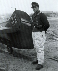 """This picture show one of the pilots who flew in the shadows of the aces. He is Unteroffizier Gerhard Proske of 1.Staffel / Jagdgeschwader 54 (JG 54) near the tail of his Messerschmitt Bf 109 G-2 """"Weiße 7"""", Werknummer 10411. Note Gruppe and Geschwader emblem under the cockpit. Picture taken on 1 October 1942 on Krasnowardeisk airfield."""