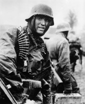 A German machine gunner marching through the Ardennes in December 1944.