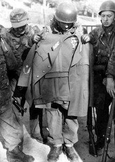 """SS paratroopers of the Battalion 500 with the Titos uniform after the company """"Rösselsprung"""" , 1944. To the left of the paratrooper stands a Brandenburger with a Wehrmacht chest eagle and a field blouse made of Italian camouflage material. Parts of the 1st Regiment (Jäger Regiment 1 """"Brandenburg"""") of Major Wilhelm Walther of the Division """"Brandenburg"""" participated."""
