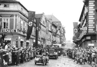 Ethnic Germans in 1938 use the Nazi salute to greet German soldiers as they enter Saaz, Czechoslovakia.