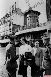 German soldiers talking with French women by the Moulin Rouge in June 1940, shortly after the German occupation of Paris.