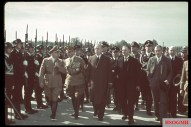 British Prime Minister Neville Chamberlain (front row, second right) walks with past an Nazi honor guard from SS-Standarte Deutschland at his reception upon arriving at Oberwiesenfeld airport (Münich) on the way to a meeting with Adolf Hitler over the latter's threats to invade Czechoslovakia, September 28, 1938. Pictured are, from left to right: Gauleiter Adolf Wagner (NSDAP-Gauleiter von München, bayerischer Minister und SA-Obergruppenführer), SA-Obergruppenführer Franz Ritter von Epp (Reichsstatthalter von Bayern), SS-Obersturmbannführer Matthias Kleinheisterkamp (Kommandeur III.Sturmbann / SS-Standarte Deutschland), Reichsminister Joachim von Ribbentrop (Reichsminister des Auswärtigen), SS-Brigadeführer Christian Weber (Inspekteur der SS-Reitschulen), Chamberlain, SS-Obergruppenführer und General der Polizei Kurt Daluege (Chef der Deutschen Ordnungspolizei), SS-Gruppenführer Reinhard Heydrich (Leiter der Politischen Abteilung der Polizeidirektion München), and Sir Neville Henderson (British Ambassador to Germany). The picture was taken by Hugo Jaeger.