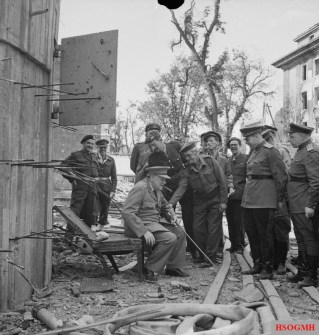 Churchill sits on a damaged chair from the Führerbunker in July 1945.