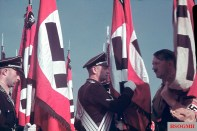 Hitler consecrating SS flags with the blood flag.