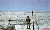 German Afrikakorps guard on duty behind barbed wire overlooking a flat desert. He is wearing short pants, tropical uniform and pith helmet with goggles. Photo taken by General Erwin Rommel during his Campaign in North Africa, 1941. There is available about 169 color slides that Rommel took during his entire Africa campaign.