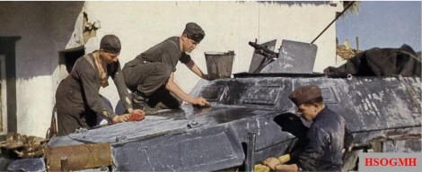 An armored crew washing their SdKfz 250 Leichter Schutzenpanzerwagen (Light-Armored Personnel Carrier). Hanging from his neck, the soldier on the left has his identification disc in a leather pouch.