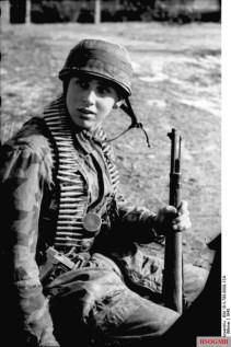 German paratrooper with rifle, pistol, stick grenade and machinegun belt in Tunisia, near the Algerian border.
