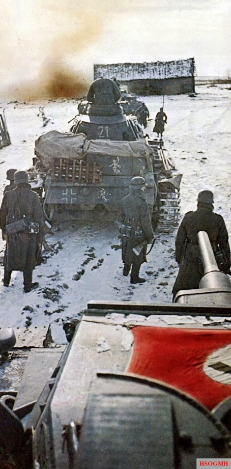 "Panzerkampfwagen III Ausf.H tanks of 11. Panzer-Division enter a Soviet village. Note the equipment covered by tarps and the extra track on the Panzer III (""21"") in the background. Behind the front tank we can see the Ghost emblem of the Division. Crews would live out of their vehicle. The Panzer III in the foreground has a Swastika flag strapped on the turret for identification by German aircraft. Soon fighting would ground to a halt as both the Germans and the Soviets would seek to survive the Russian winters."