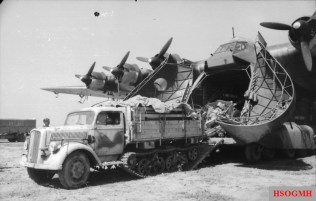 Opel Maultier towing an artillery piece onto or off an Me-323.