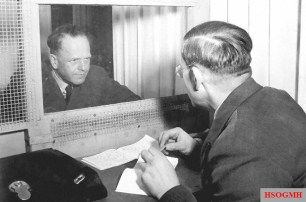 Erhard Milch, facing camera, confers with his brother, Dr. Werner Milch in the special consulting room provided for defendants on trial at Nurenberg.