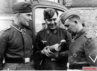 Unteroffizier Erich Heintze (left) and Gefreiter Arnold Huebner (right), in a conversation with a radio war correspondent, April 1942. They were just received the coveted Ritterkreuz des Eisernen Kreuzes (Knight's Cross of the Iron Crosses) a month before, in 7 March 1942. Heintze as a Geschützführer, while Huebner as a Richtkanonier. Both from 3.Batterie / I.Abteilung / Flak-Regiment 33 (motorisiert). The picture was taken by Bildberichter Eisenhardt.