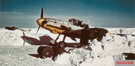 """Photographed in the winter of 1941/42, this """"White 2"""", a Messerschmitt Bf 109F-2 of 7.Staffel / III.Gruppe / Jagdgeschwader 53 (JG 53) """"Pik-As"""", is standing in the partial shelter of a bay of snow."""