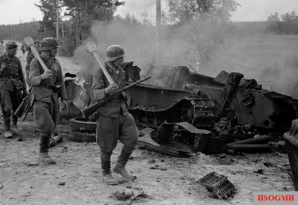 Finnish soldiers marching next to a destroyed Soviet T-34 tank.