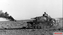 Afrika Korps Panzer III advances past a vehicle burning in the desert, April 1941.