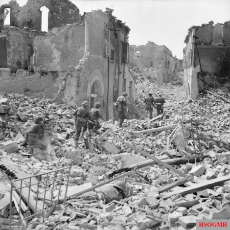British troops of the 5th (Huntingdonshire) Battalion, Northamptonshire Regiment, part of 11th Brigade of 78th Division, pick their way through the ruins of Argenta, 18 April 1945.