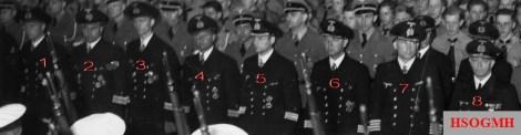 """Hitlerjugend demonstration under the banner of """"Die Ritterkreuzträger der Kriegsmarine Rede an die Hitlerjugend"""" (The Knight's Cross Recipients of the German Navy Speech to the Hitler Youth) at the Berlin Sportpalast, 16 June 1943. From left to right: 1. ??? 2. ??? 3. Kapitänleutnant Reinhard Hardegen (Kommandant U-123) 4. ??? 5. ??? 6. ??? 7. Kapitän zur See Kurt Thoma (Chef Abteilung K III M im Oberkommando der Marine) 8. Admiral Walter Warzecha (Chef des Allgemeinen Marinehauptamtes)."""