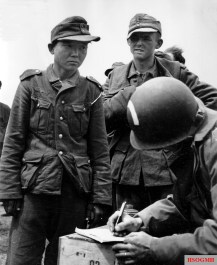 Yang Kyongjong, a foreign volunteer in the army with his German comrades after the capture at Utah Beach on June 6, 1944. The men are members of an Airborne Division of the United States Army that are registering the prisoners of war.