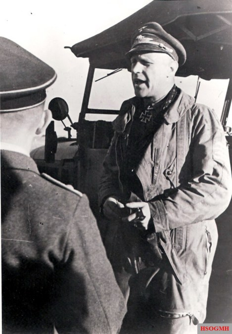 Kampfflieger (bomber pilot) Major Reinhard Günzel briefs his men at the front, while wearing a fliegerkombi.