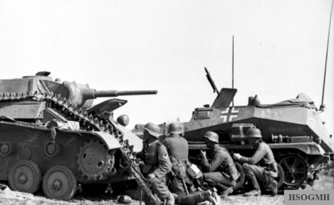 German troops take cover behind a knocked out T-70 light tank and beside a Sd.Kfz. 250 halftrack, summer 1942.