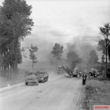Carriers and armoured cars pass burning German transport on the road to Brussels, 3 September 1944.