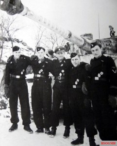 """This picture shows Wittmann with his crew, from left to right. SS-Panzerschütze Werner Irrgang (Funker), SS-Rottenführer Bobby Woll (Richtschütze), SS-Untersturmführer Michael Wittmann (Zugführer in 13.Kompanie (schwere) / IV.Abteilung / SS-Panzer-Regiment 1 / 1.SS-Panzer-Division """"Leibstandarte SS Adolf Hitler""""), SS- Panzerschütze Sepp Rößner (Ladeschütze), and SS-Sturmmann Eugen Schmidt (Fahrer). Behind them is Wittmann's Panzerkampfwagen VI Tiger I Ausf.F S04, with 88 victory rings on its barrel. Actually the Ritterkreuz recommendation sent by Divisionskommandeur Wisch to the Oberkommando der Wehrmacht (OKW) on 10 January 1944 """"only"""" included Wittmann's winnings as 66 tanks, but something incredible happens: in the four day span between the submission of the proposal to the official approval notification, this tank master went berserk and destroyed no fewer than 22 additional tanks to hoist his winning score to a total 88!"""