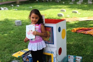 A young girl holds up a book she picked from the Little Free Library