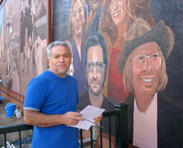Emanuel poses with Red Rocks stars Bono and John Denver as the mural nears completion.