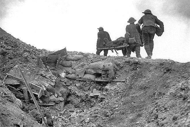 Soldaten halen een gewonde Brit uit een veroverde Duitse loopgraaf - Foto:  Imperial War Museums