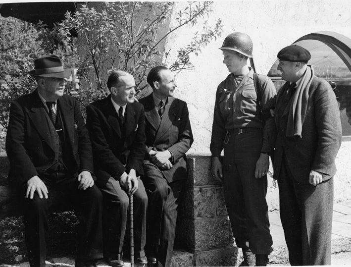 Iemand van de militaire politie van het Zevende Leger praat na hun bevrijding met (van links naar rechts), Léon Jouhaux, François de La Rocque, Jean Borotra en Marcel Granger.