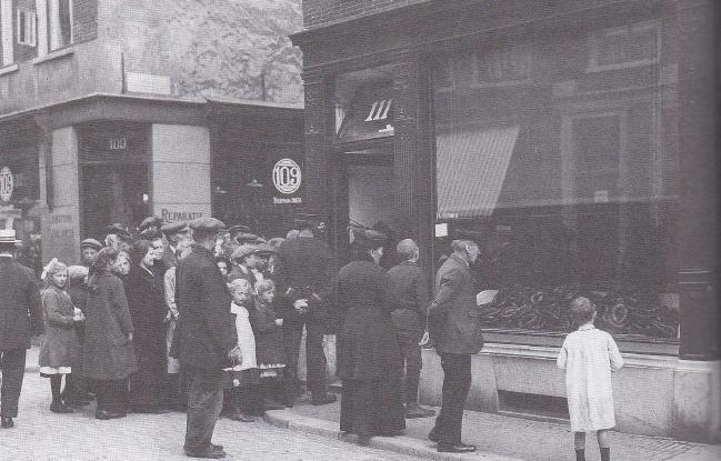 Klanten staan voor een slagerij in de Kleine Houtstraat in Haarlem in mei 1918 in de rij voor eenheidworst.
