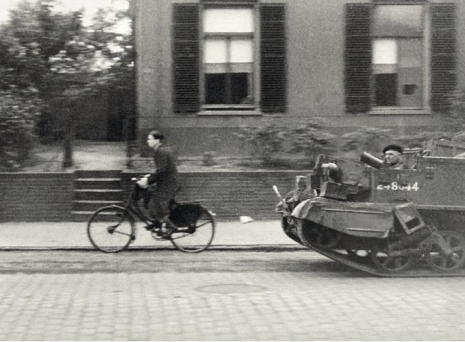 Een jongeman op een fiets rijdt op 18 september in Nijmegen voor een Britse carrier uit over de St. Annastraat, waarschijnlijk als gids. - © uit: De bevrijding in Beeld  / Vantilt fragma