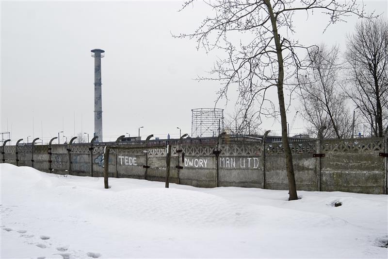 Muur om het voormalige fabrieksterrein van IG-Farben en de carbidtoren. De toren is inmiddels gesloopt en het fabrieksterrein wordt heringericht. © Hans Citroen