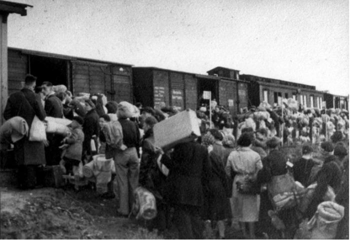 Mensen staan bepakt en bezakt te wachten bij de goederenwagons van een trein in doorvoerkamp Westerbork, 1942-1945