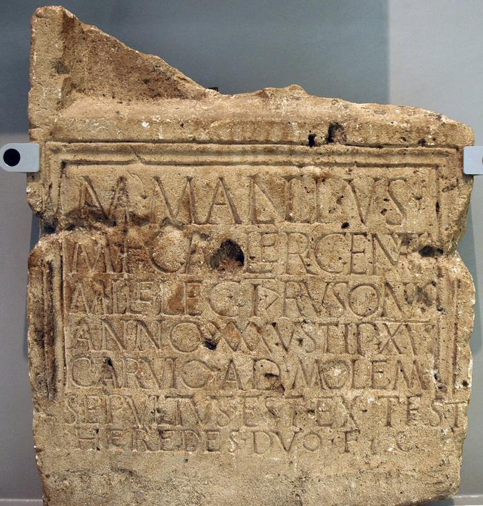 Inscriptie uit Herwen: het graf van een soldaat Mallius. In de derde regel zijn onderdeel, het Eerste Legioen. (Valkhofmuseum, Nijmegen)