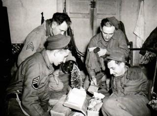 Amerikaanse militairen van de 3rd Division in Italië pakken op 16 december 1943 hun kerstpakketjes van thuis uit. © US Army Center of Military History